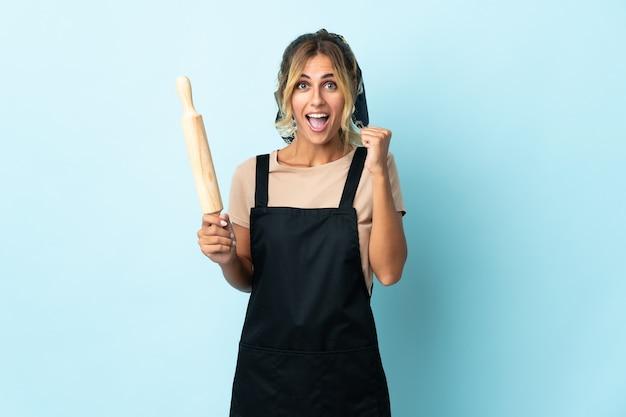 Молодая блондинка уругвайская кулинария женщина на синем празднует победу в позиции победителя