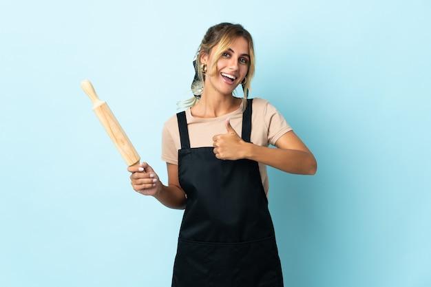 Молодая блондинка уругвайская кулинария женщина на синем, показывая большой палец вверх