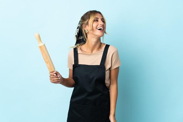 Молодая блондинка уругвайская кулинария женщина на синем смехе