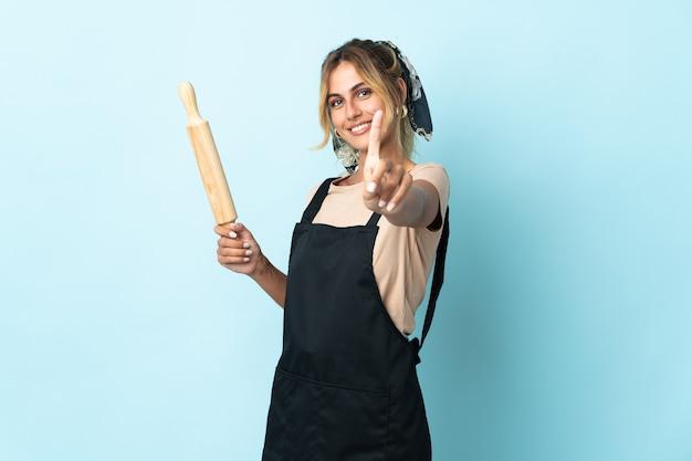 Молодая блондинка уругвайская кулинария женщина на синем, показывая и поднимая палец