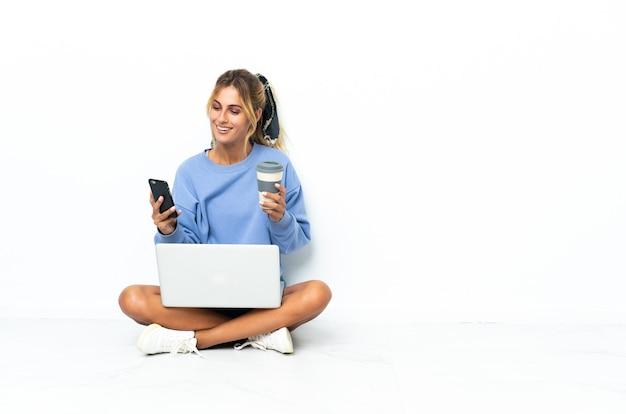 Молодая блондинка уругвайская девушка с ноутбуком, изолированным на белой стене, держа кофе на вынос и мобильный