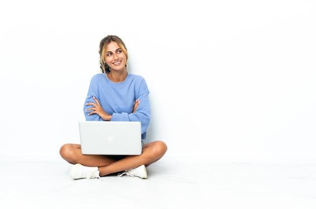 Молодая блондинка уругвайская девушка с ноутбуком на белом, глядя вверх, улыбаясь