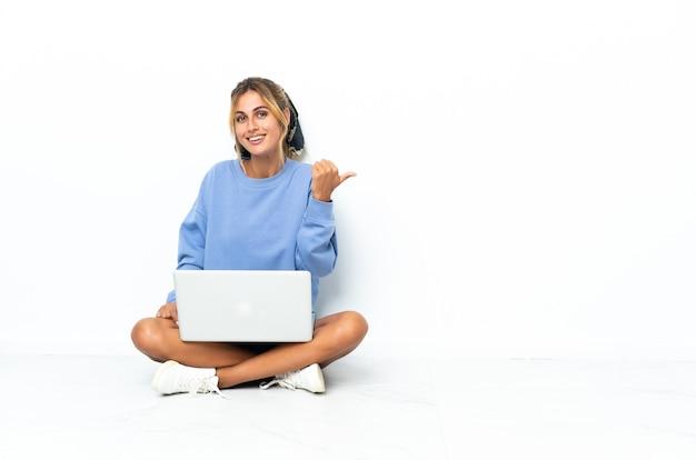 Молодая блондинка уругвайская девушка с ноутбуком на белом, указывая в сторону, чтобы представить продукт