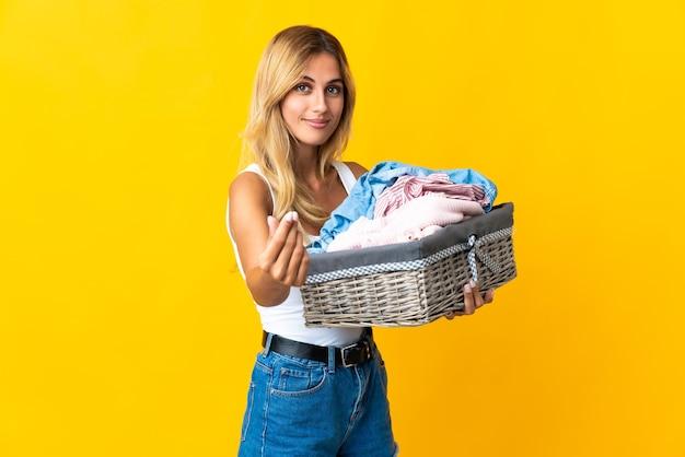 Молодая блондинка уругвайская женщина держит корзину с одеждой на желтом, делая деньги жест