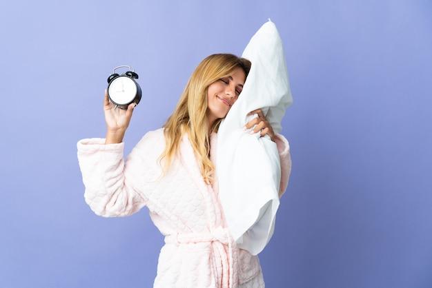 Молодая блондинка уругвайская женщина изолирована на синей стене в пижаме и держит часы и подушку со счастливым выражением лица