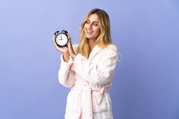 Молодая блондинка уругвайская женщина изолирована на синей стене в пижаме и держит часы с счастливым выражением лица
