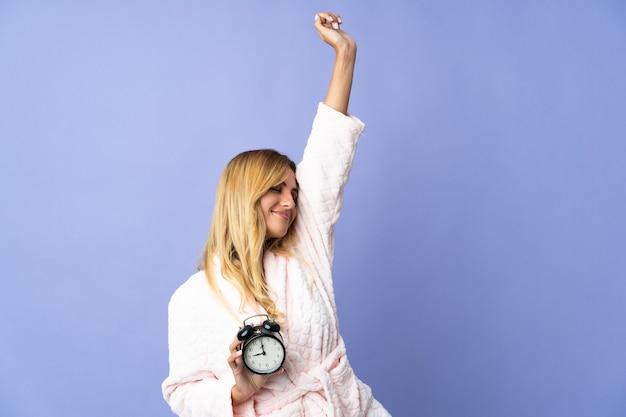 パジャマと幸せな表情で時計を保持している青い壁に分離された若い金髪のウルグアイの女性