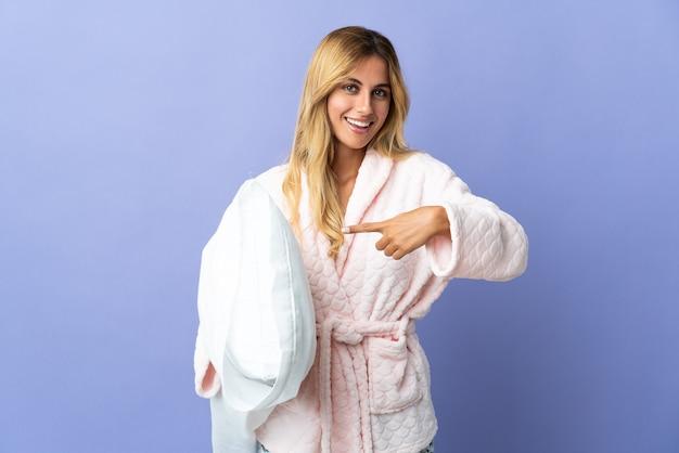 Молодая блондинка уругвайская женщина изолирована на синей стене в пижаме и указывает подушку