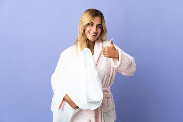 Молодая блондинка из уругвая изолирована на синей стене в пижаме и с большими пальцами руки вверх, потому что произошло что-то хорошее