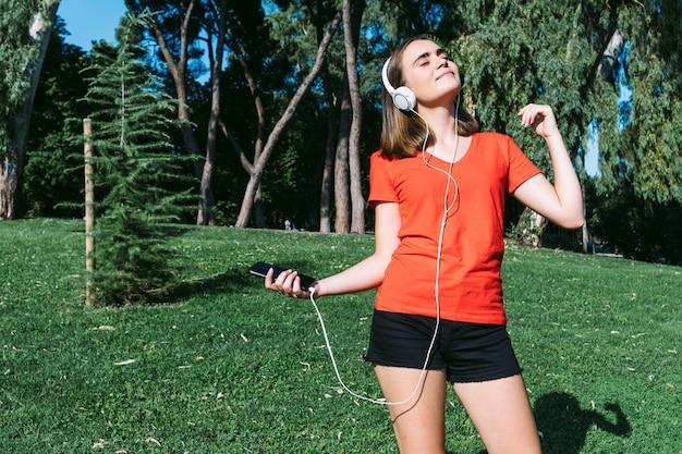 Молодая блондинка в красной рубашке чувствует себя свободно, слушая музыку в наушниках в парке