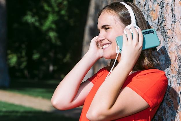 Молодая блондинка в красной рубашке смотрит на мобильный телефон и слушает музыку в парке