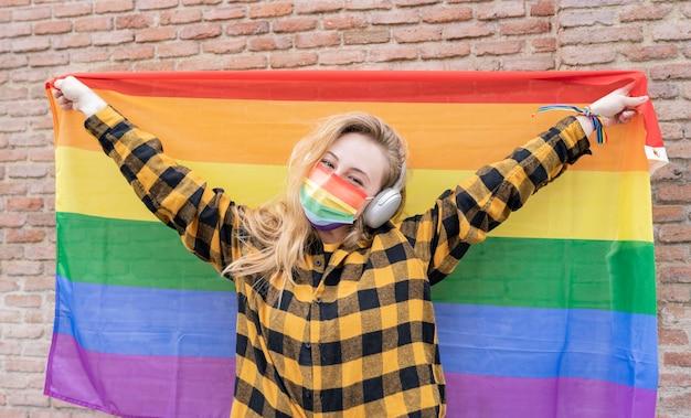 Lgbtの集団に抗議する通りで虹色の旗を持つ若いブロンド。