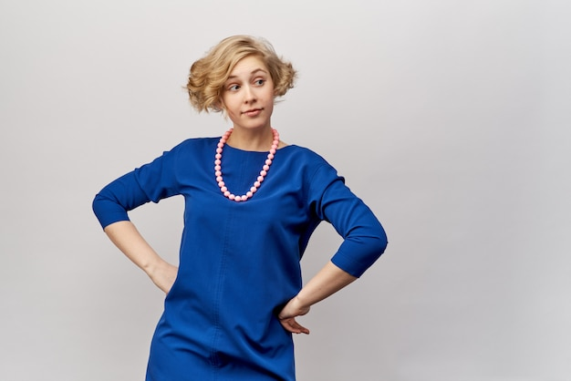 Young blonde with short hair and curls, posing for studio shooting. she's wearing a blue dress and vintage beads. friendly facial expression and glance to the side. hands rested on her hips.