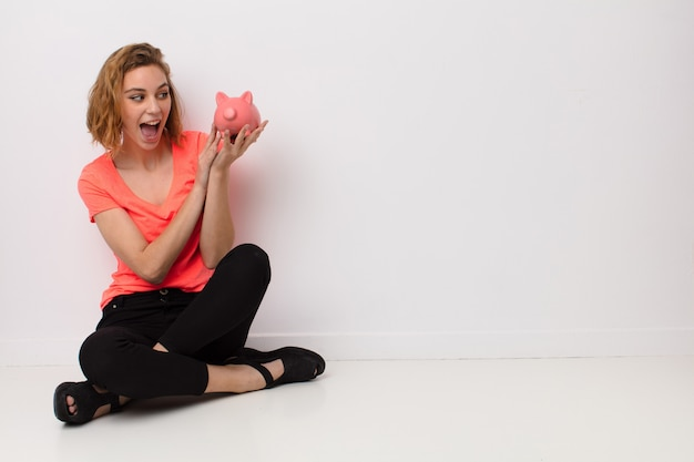 Young blonde woman  against flat color wall with a piggy bank