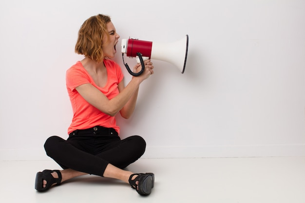 Young blonde woman  against  wall with a megaphone