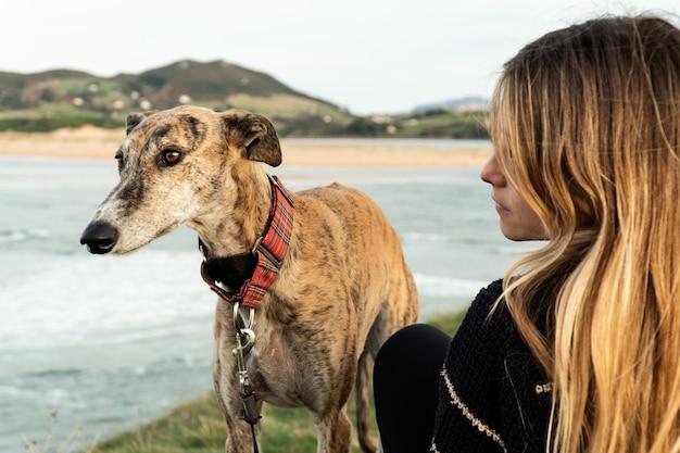 Молодая блондинка и ее борзая на берегу