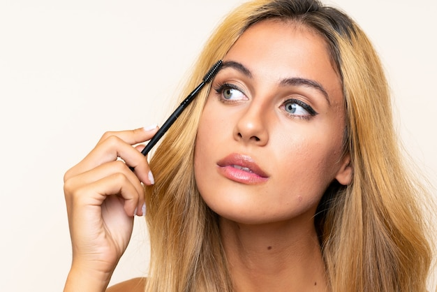 Young blonde woman applying mascara with cosmetic rush