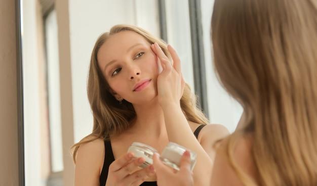 Молодая блондинка наносит увлажняющий крем на лицо, ежедневная косметика по уходу за кожей красоты