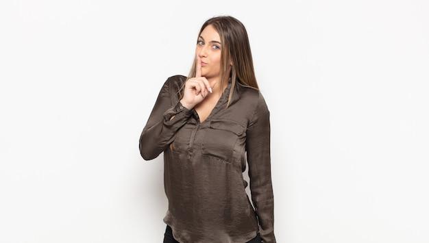 沈黙と静けさを求め、口の前で指で身振りで示す、shhと言うか秘密を守る若いブロンドの女性