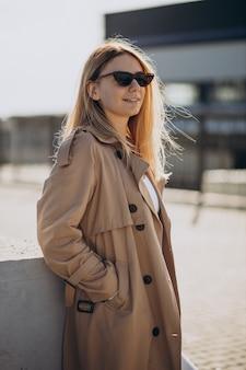 Young blonde woman in beige coat walking in the street