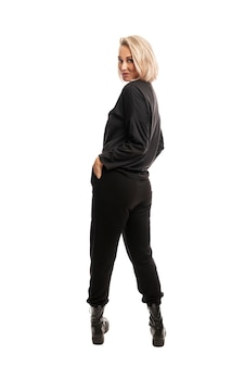Young blonde woman in black casual suit and rough boots. full height. back view. isolated
