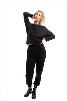 Young blonde woman in black casual suit and rough boots. full height. isolated