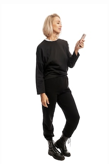 Young blonde woman in black casual suit and rough boots with a phone in her hand. full height. isolated