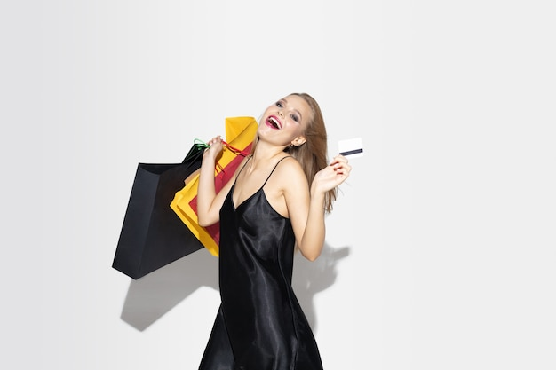 Young blonde woman in black dress shopping on white wall