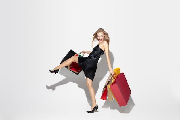 Giovane donna bionda in abito nero, shopping su bianco