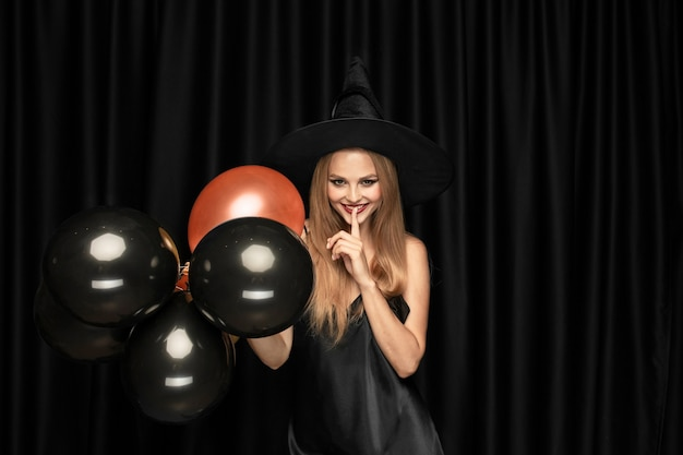 Young blonde woman in black hat and costume on black background. attractive, sensual female model. halloween, black friday, cyber monday, sales, autumn. copyspace