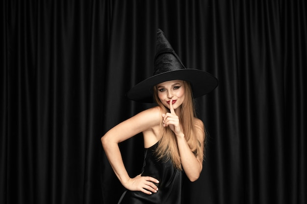 Young blonde woman in black hat and costume on black background. attractive, sensual female model. halloween, black friday, cyber monday, sales, autumn
