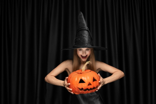 Young blonde woman in black hat and costume on black