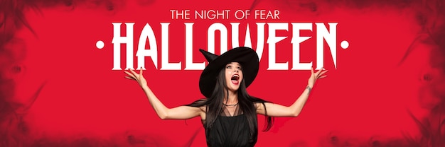 Young blonde woman in black hat and costume on red background. attractive caucasian female model holding banner halloween. black friday, cyber monday, sales, autumn concept. flyer for your ad.