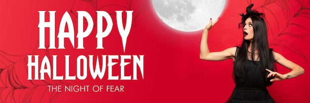 Young blonde woman in black hat and costume on red background. attractive caucasian female model holding moon. halloween, black friday, cyber monday, sales, autumn concept. flyer for your ad.