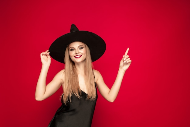 Young blonde woman in black hat and costume on red background. attractive caucasian female model posing. halloween, black friday, cyber monday, sales, autumn concept. copyspace. pointing, showing.