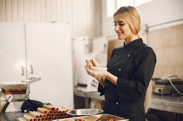 Young blonde woman in black uniform in kitchen of restaurant preparing different sweets and cookies.