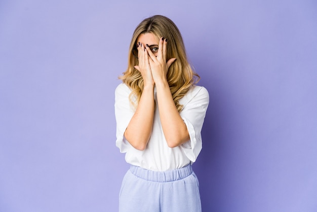 Young blonde woman blink through fingers frightened and nervous