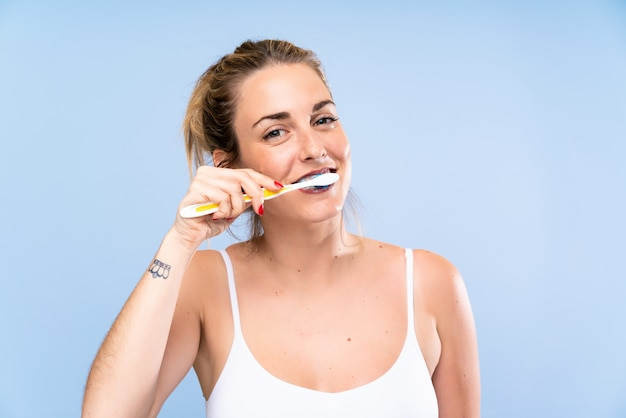 Young blonde woman brushing her teeths