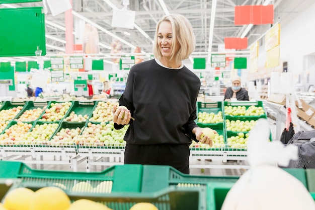 Young blonde woman buys fruit in the supermarket.