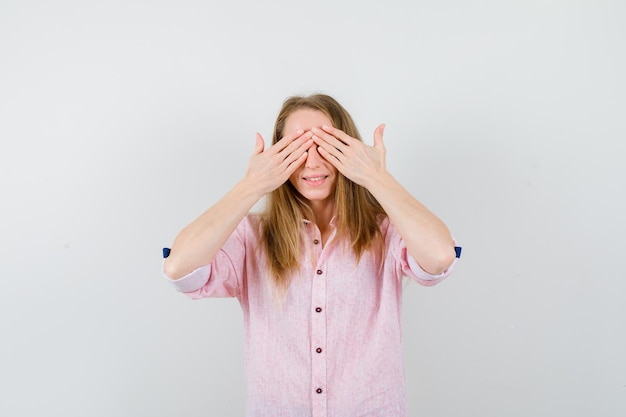 Young blonde woman in a casual pink shirt covering her eyes