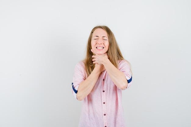 Giovane donna bionda in una camicia rosa casual con mal di gola