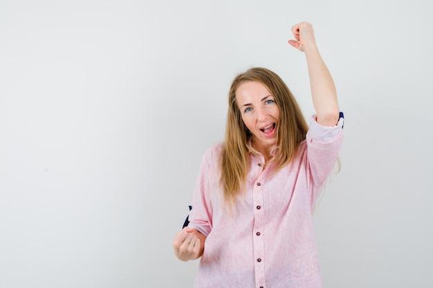 Giovane donna bionda in una camicia rosa casual