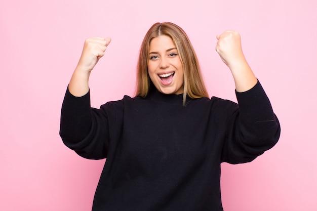 Молодая блондинка празднует невероятный успех как победительница, выглядит взволнованной и счастливой и говорит: «бери!» против плоской стены