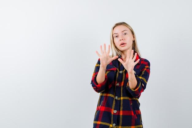 Giovane donna bionda con una camicia a scacchi