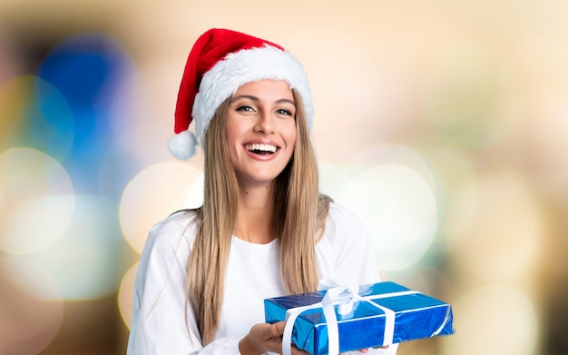 Young blonde woman in christmas holidays on unfocused wall