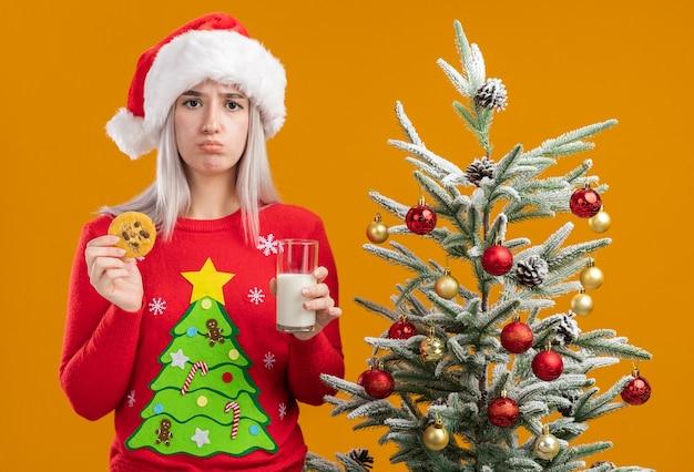 Giovane donna bionda in maglione di natale e cappello della santa che tiene un bicchiere di latte e biscotto con espressione triste