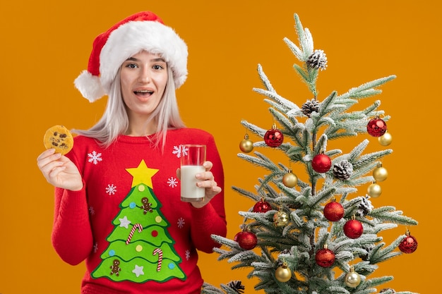 Young blonde woman in christmas  sweater and santa hat holding glass of milk and  cookie  with smile on face  standing next to a christmas tree over orange  wall