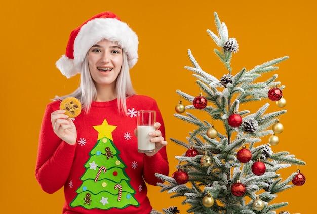 Giovane donna bionda in maglione di natale e cappello della santa che tiene un bicchiere di latte e biscotto con il sorriso sul viso