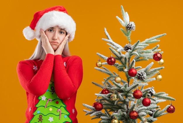 Giovane donna bionda in maglione di natale e cappello da babbo natale guardando la fotocamera con espressione triste con le braccia sulle guance in piedi accanto a un albero di natale su sfondo arancione