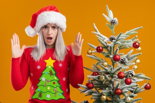 Giovane donna bionda in maglione di natale e cappello di babbo natale con la faccia arrabbiata che alza le mani in piedi accanto a un albero di natale sopra il muro arancione